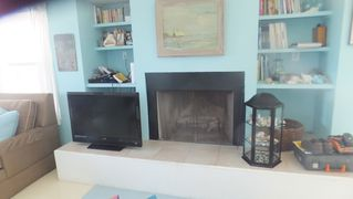 Galveston house photo - Fireplace and TV, Books and games on shelves.