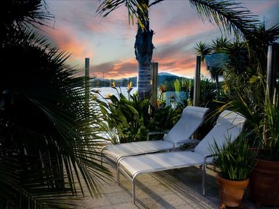 Enjoy sunset views on the waterfront deck as the palms flutter in the breeze