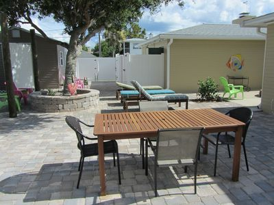 Outdoor dining table with lounge area and shade tree behind