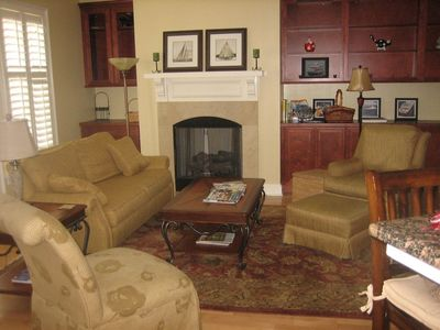 Comfortable seating in living room  with built in bookshelves and gas fireplace
