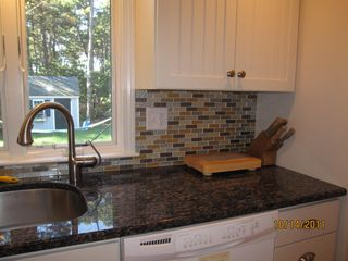 Wellfleet house photo - Granite countertop and glass tiled backsplash with Grohe pullout faucet