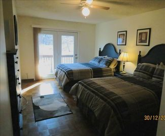 Main level bedroom with 2 full size beds, large closet, tv/dvd player, & deck