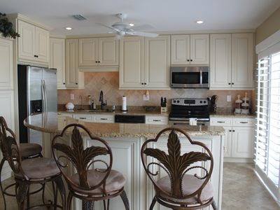 Fully stocked kitchen with stainless steel appliances and 2 tier island
