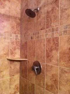 Master Bath shower with floor to ceiling porcelain tile and comfort seat