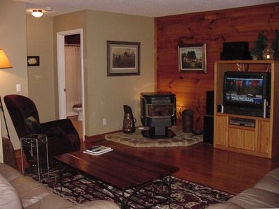 Living room has wood pellet stove and entertainment center