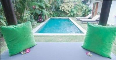 Pool surrounded by tropical foliage and lounge chairs