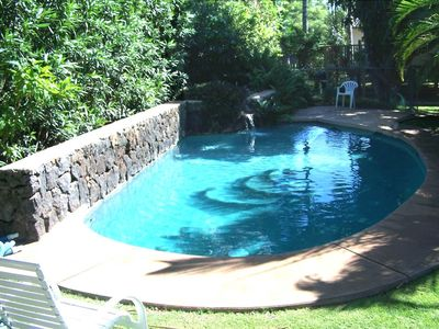 Swimming pool with waterfall. Pool is fenced and gated.