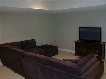 Downstairs entertainment room with flat screen TV