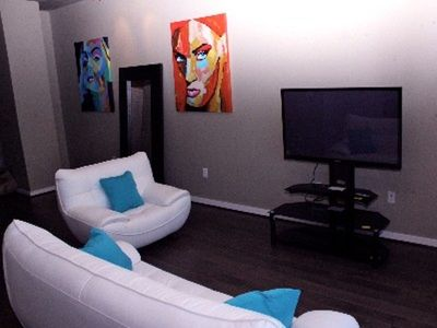 Posh Oversized Artwork and 50in Samsung flatscreens in living and bedroom.
