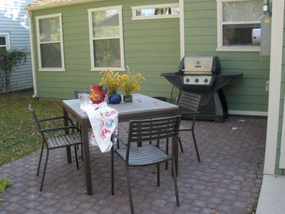 Patio just outside the back door with table and chairs and gas grill