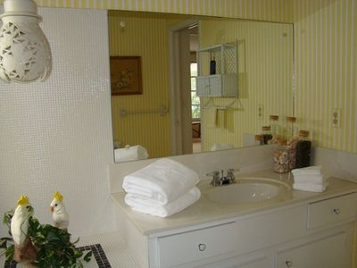 A sunny hall bathroom with a shower over tub.
