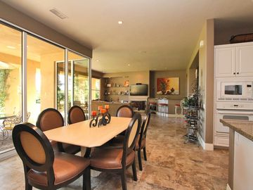 Dining room with retractable doors opening onto large patio and pool area