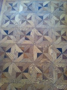 The hardwood floors have been re-finished to highlight the inlay pinwheel patten
