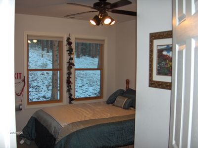 bedroom with queen bed with views into the pines