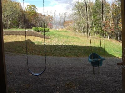 Swings for kids under deck and near paver patio.