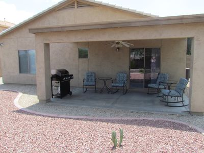 Patio with gas BBQ grill and two seating areas.