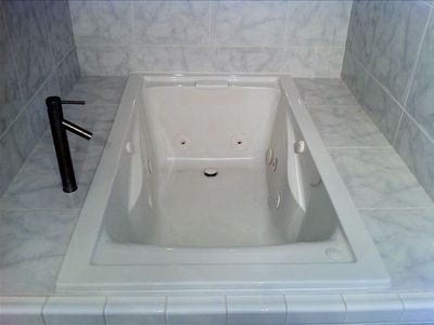 "Extra deep 60"" x 32"" jacuzzi tub encased in white marble"