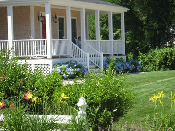 Wrap around farmers porch over looking hydrangea plants and pool