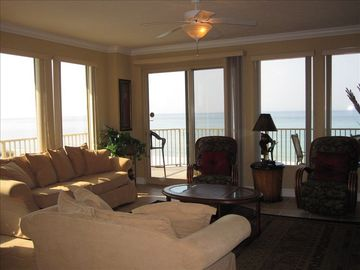 Living room with balcony access and ocean view.