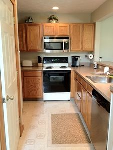 Kitchen with new stainless steel microwave and Bosch dishwasher