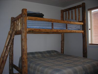 Main level bedroom with custom twin log bunk over queen.