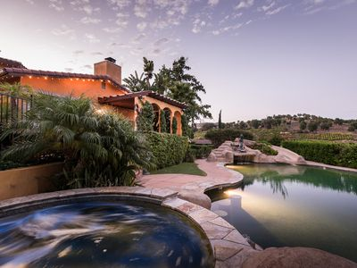 Solar heated saltwater pool, including waterfall, water slide, grotto, bar