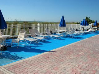 Indian Rocks Beach condo photo - Deck area with lounge chairs with Gulf beaches at backdrop