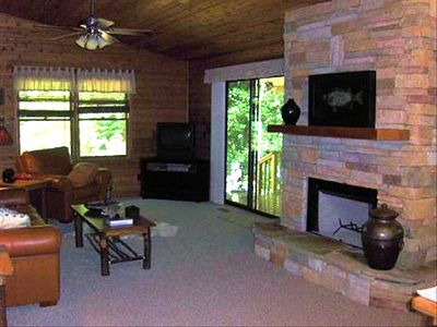 Living area with wood-burning fireplace - sliding door leads to creek