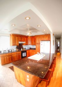 Modern kitchen features a breakfast bar and dining area w/ table- granite tops