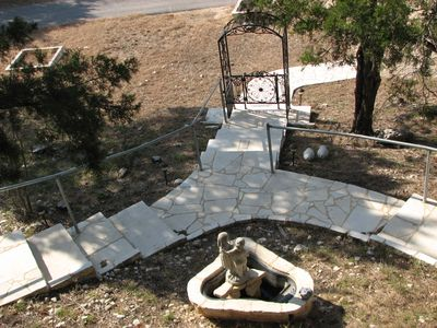 Stone staircase to the house and lower porch with fountain in the middle.