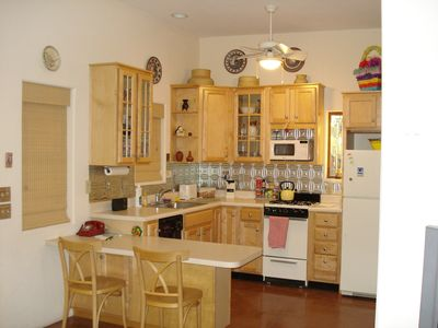 Full kitchen with dishwasher, gas range, dishes, pots and pans, coffee maker