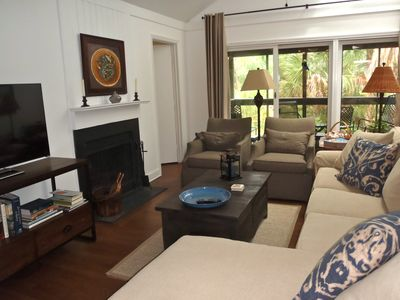 Living area with TV, fire place, sectional sofa, and view to screened porch.