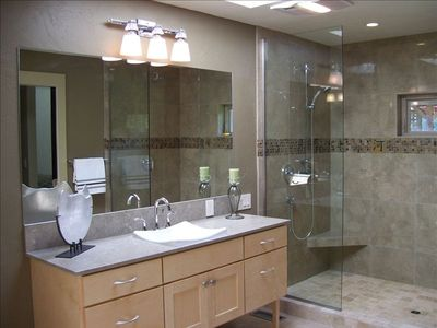 Master bath with two vanities and dual head walk in glass wall & granite shower.