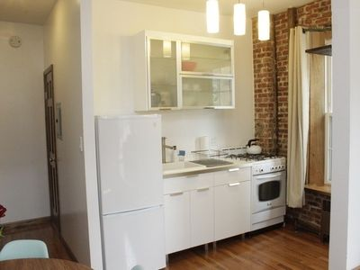 Modern Kitchen. Exposed Brick Wall. High Ceilings. Hard Wood Floors.