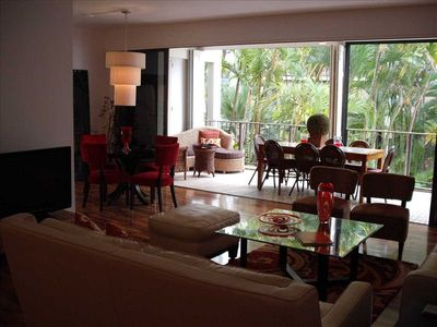 VIEW TO FURNISHED LANAI W/ ADDITIONAL DINING TABLE FOR 8, SOFA, CHAIRS AND BAR