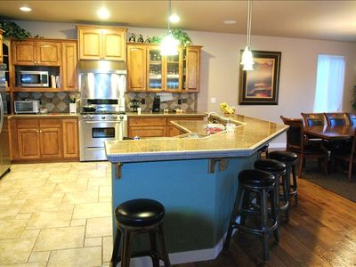 "Kitchen. Professional series, 36"" gas stove and grill top). 6 barstool counter."