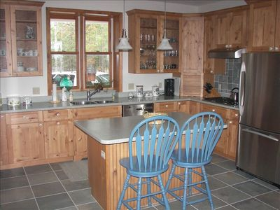 Fully Equipped Custom Kitchen with Breakfast Island and Window to the Woods