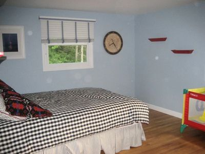 another large bedroom with queen bed, bunks, and optional toddler bed & crib