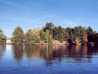 Stoney Lake cottage photo - Approaching island's western tip: Sleeping Cabin (left), Swimming Dock (center)