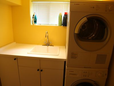 laundry room with new Bosch washer/dryer, laundry detergent and fabric condition