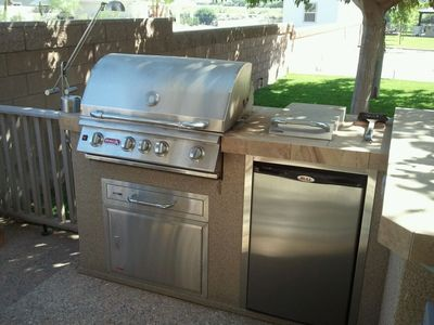 BBQ island on the front patio of home includes BBQ, sideburner and refrigerator.