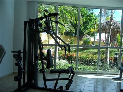 Air conditioned gym with a common area with tables, chairs and bathrooms.