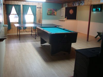 First level game room with pool table, ping-pong, darts and wood stove