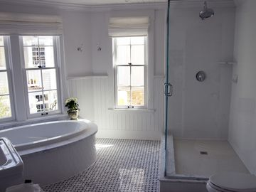 Rear master bathroom with two pedestal sinks, soaking tub, shower, and a view.