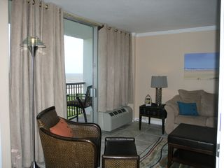 Galveston condo photo - Family room with leather chair, ottoman and balcony overlooking the beach.