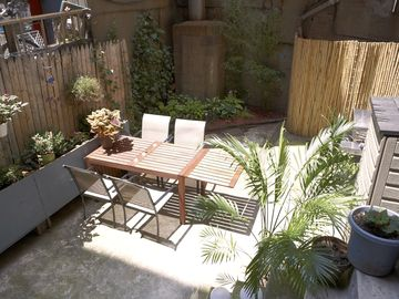 backyard with table and one leaf open for 6 with 4 chairs