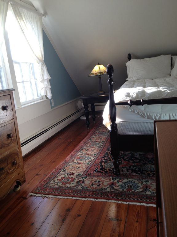 Master bedroom furnished with antique bed and a TempurPedic mattress.