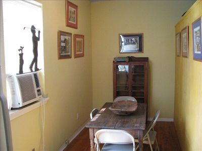 Bay St. Louis studio rental - dining area with handmade pine table, oak china and decorated with Moseley art.