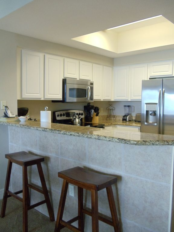 Well equipped kitchen with granite countertops and stainless steel appliances.