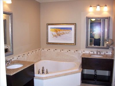 Custom bathroom with dual sinks, large shower and jetted tub